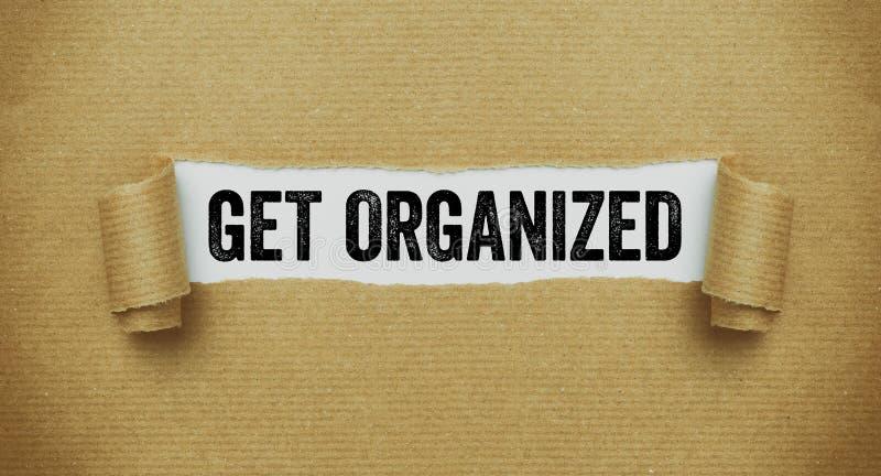 Papel marrón rasgado que revela las palabras Get organizado imagenes de archivo