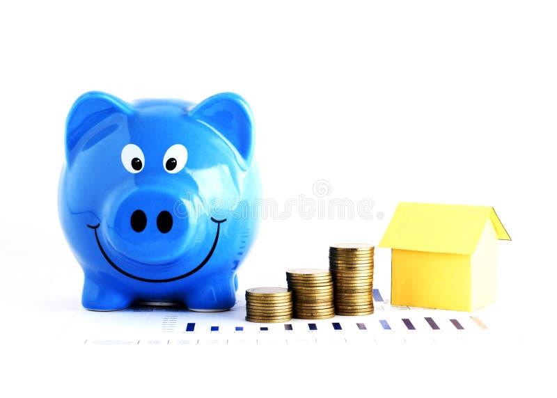 Papel mealheiro e da pilha e da casa azuis das moedas para os empréstimos hipotecarios c imagem de stock