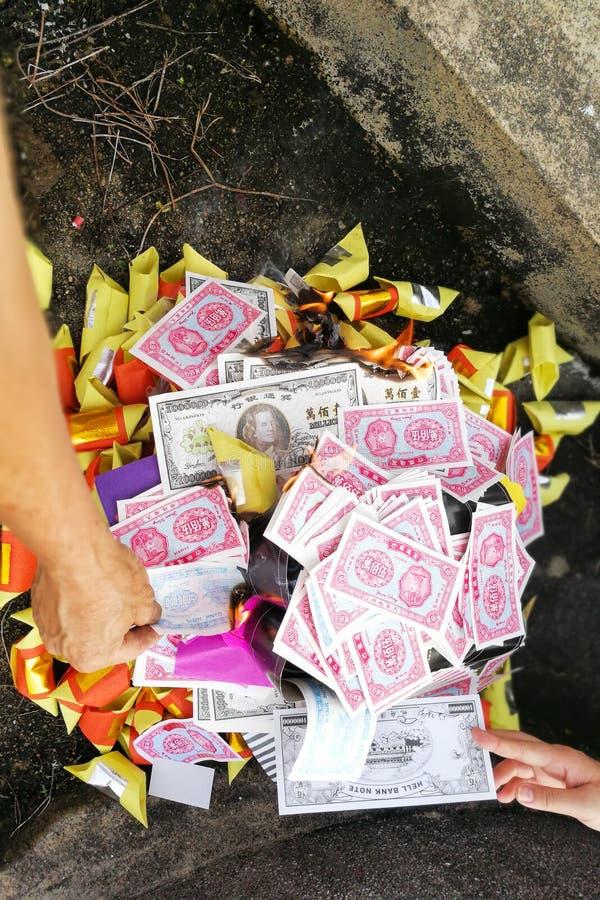 Papel moeda e ouro chineses da queimadura da tradição do taoism aos antepassados imagem de stock