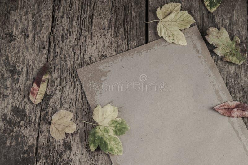 Papel na tabela de madeira decorada com folhas secadas fotos de stock