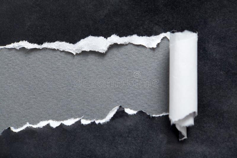 Papel negro rasgado con el espacio gris para el mensaje imagen de archivo libre de regalías