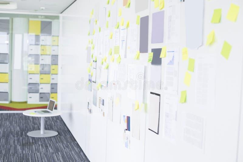 Papel para cartas pegajosos na parede no espaço de escritórios criativo fotos de stock