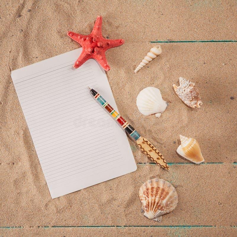 Papel para las notas cerca de conchas marinas en fondo de la arena Copie el espacio fotos de archivo