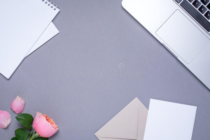 Papel pintado gris con la tarjeta de regalo, la rosa rosada y el ordenador portátil imagenes de archivo