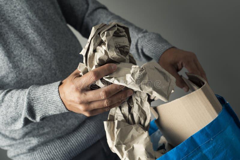 Papel que lanza del hombre al cubo de la basura de reciclaje fotos de archivo libres de regalías