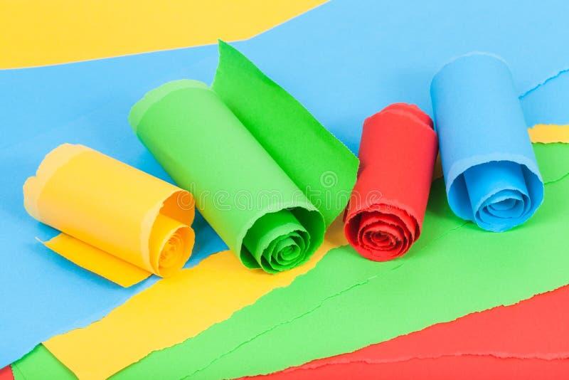 Papel rolado da cor em folhas do papel rasgado imagens de stock