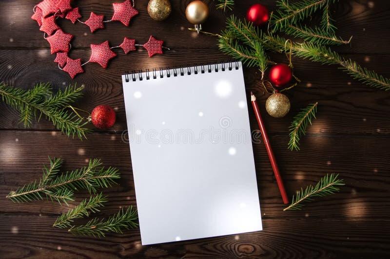Papel vacío blanco de la libreta con la decoración de la Navidad en un de madera foto de archivo