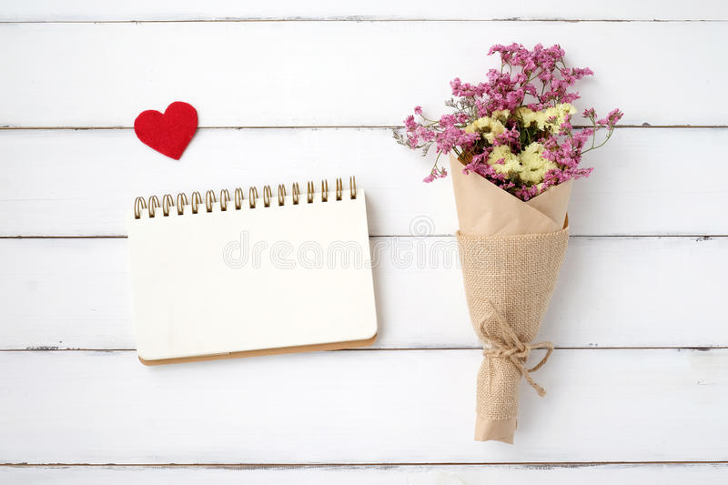 Papel vazio do livro de nota, forma do coração da tela e ramalhete da flor sobre fotos de stock