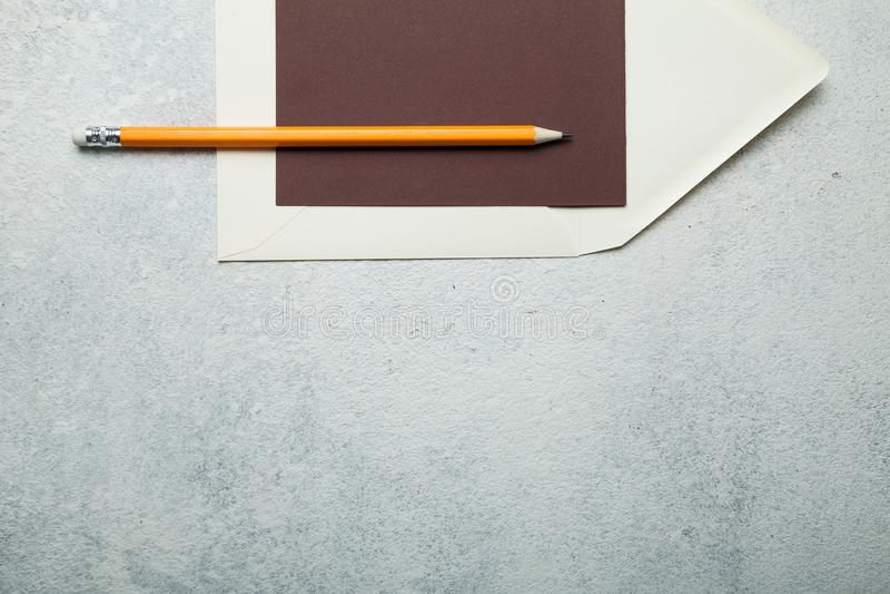 Papel vazio para o marrom do texto, envelope bege e lápis ha contra o fundo branco fotografia de stock royalty free
