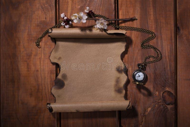 Papel velho com os relógios no fundo de madeira imagem de stock royalty free