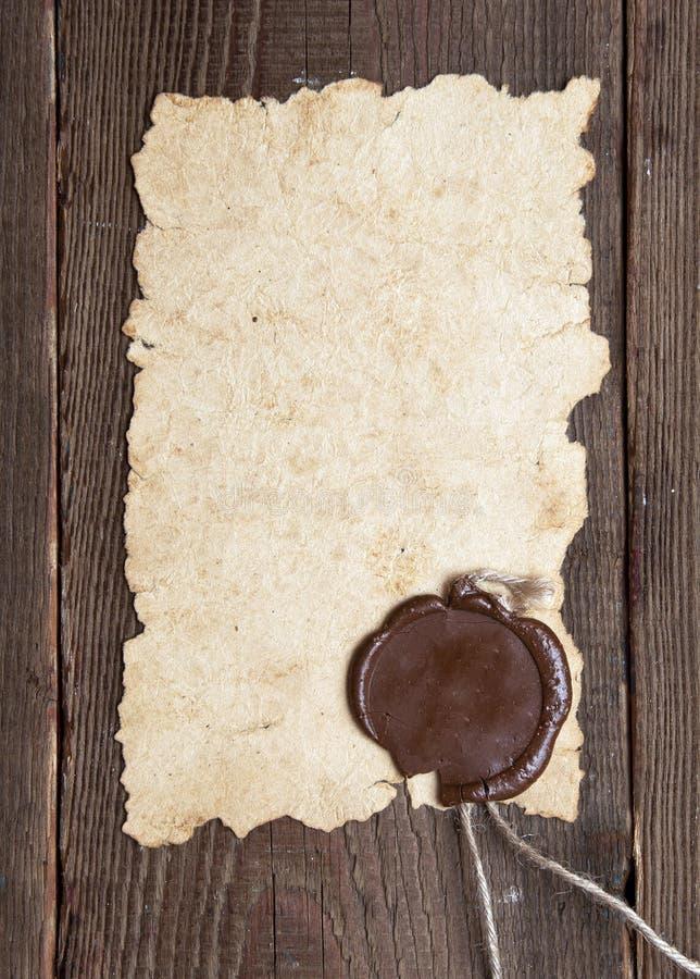 Papel velho com um selo da cera na textura de madeira marrom fotos de stock royalty free