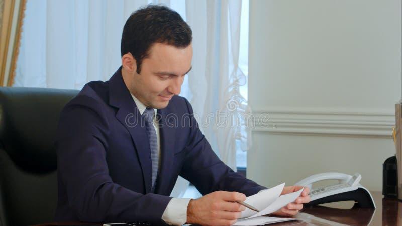 Papeleo joven de la lectura del hombre de negocios en el escritorio en oficina y la sonrisa imagenes de archivo