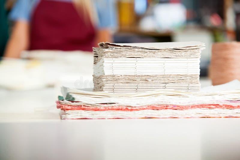 Papeles apilados listos para hacer las libretas en la tabla fotos de archivo libres de regalías