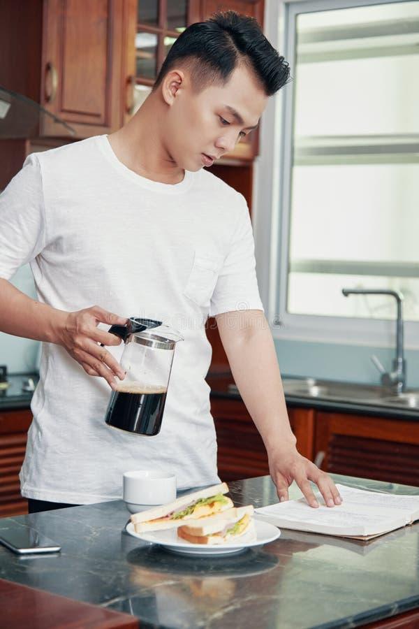 Papeles asiáticos jovenes de la lectura del hombre durante el desayuno fotografía de archivo