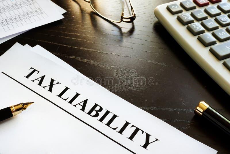 Papeles con deuda impositiva del título en un escritorio foto de archivo libre de regalías