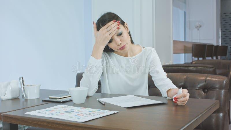 Papeles de estornudo y de firma de la mujer de negocios enferma y cansada en un café imagenes de archivo
