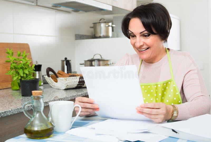 Papeles de firma del ama de casa en cocina foto de archivo