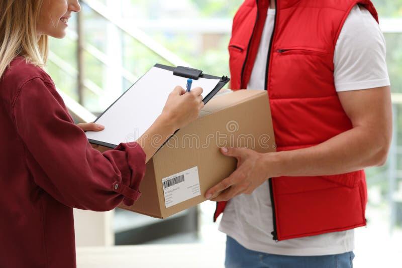 Papeles de firma de la mujer joven para el paquete entregado dentro fotografía de archivo libre de regalías