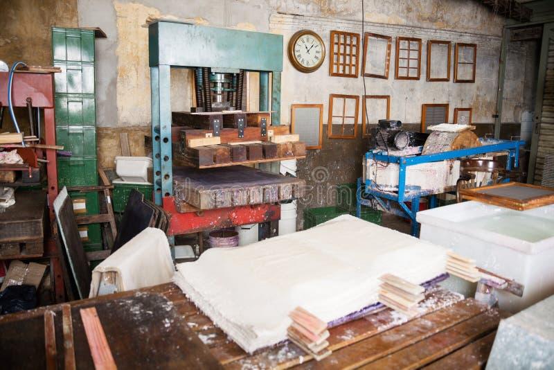 Papeles y máquina de la prensa en fábrica imágenes de archivo libres de regalías