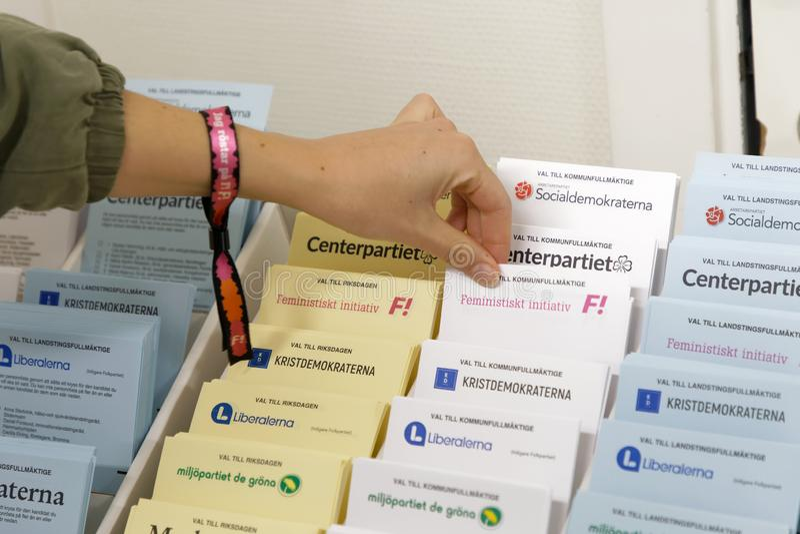 Papeletas electorales de Selectiing antes de votar en la interrogación-cabina en t foto de archivo libre de regalías