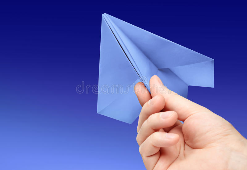 Paper airplane. Hand launches paper airplane on background sky royalty free stock photo