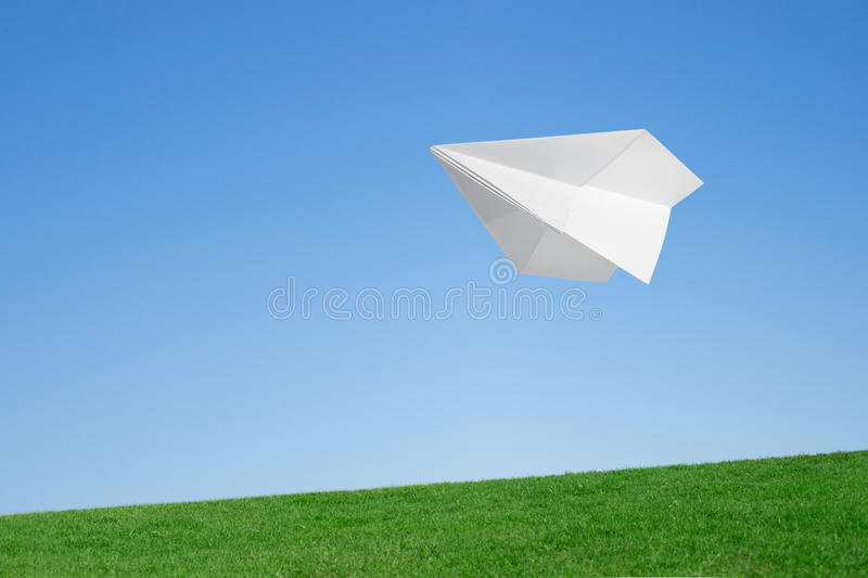 Paper airplane. Flying over the lawn against the blue sky stock images