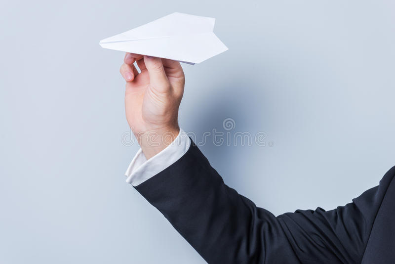 Paper airplane. Close-up of man in formalwear holding paper airplane against grey background royalty free stock image