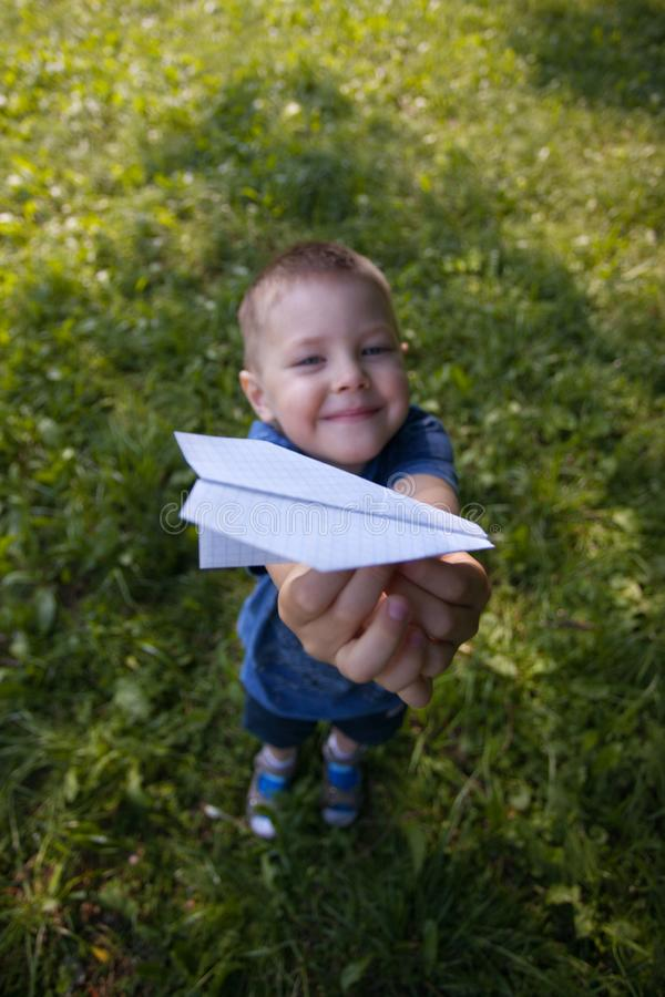 Paper airplane in kid hands close-up. Toddler boy 4 years old holding origami plane in park or garden in shadoow in summer sunny stock images