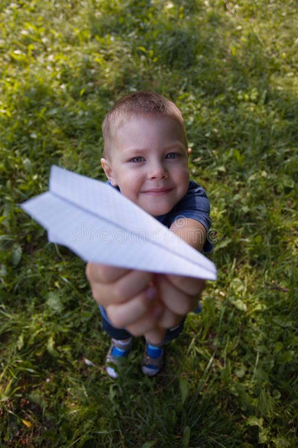 Happy laughing child hold paper ship indoors. Green field background. Happy childhood, summer, holiday, travel, vacation concept. royalty free stock photography