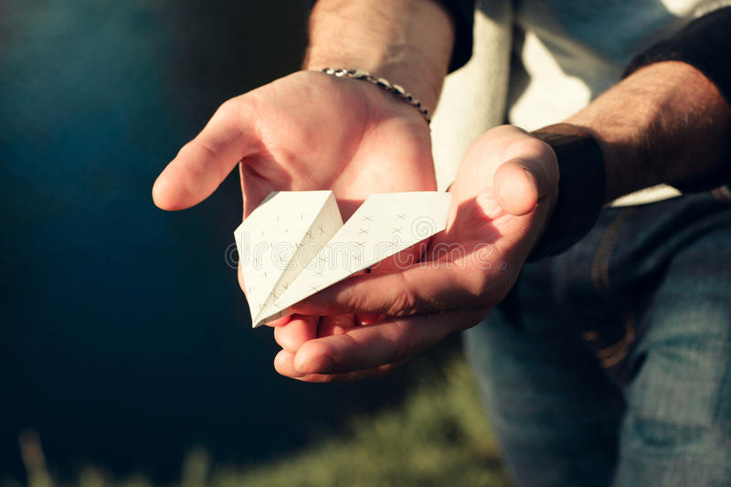 Paper airplane in male hands close-up. Man holding origami plane in palms outdoor near river. Hobby, leisure, entertainment, handmade, craft concept royalty free stock images