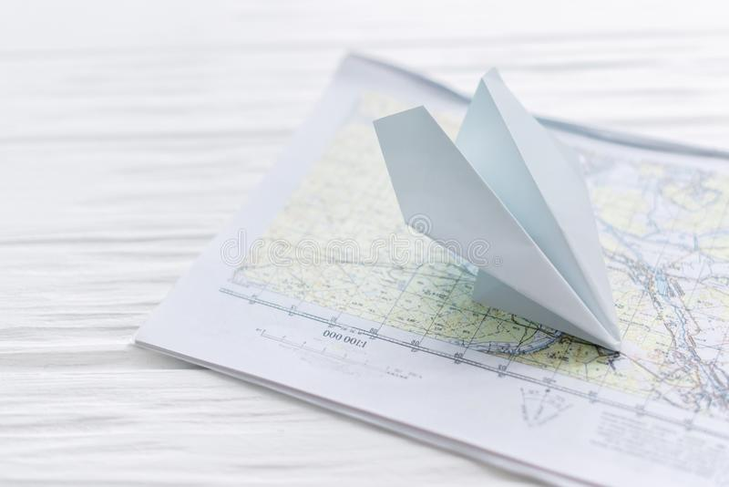 Paper airplane, on a map on a wooden background.  royalty free stock photography