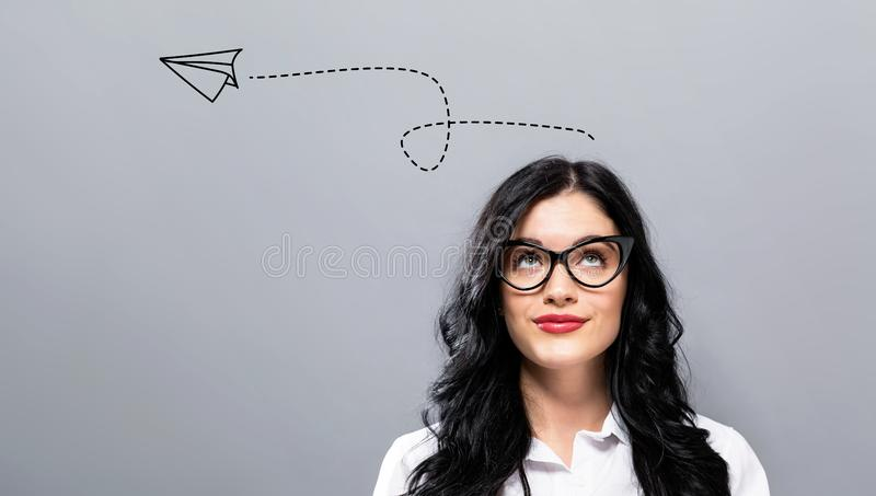 Paper airplane with young businesswoman stock photo