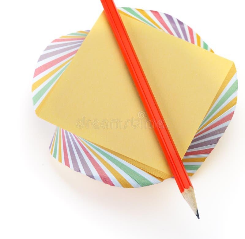 Paper anmärkning och en röd blyertspenna royaltyfria bilder