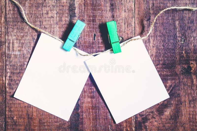 Paper attach to rope with clothes pins on wooden background. Paper attach to rope with clothes pins on a wooden background royalty free stock image