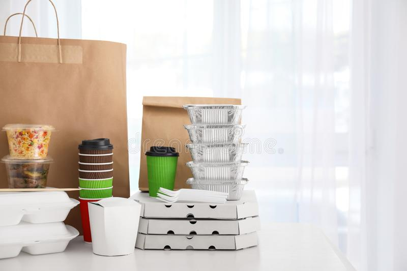 Paper bag, boxes and coffee cups on table against light background. Food delivery royalty free stock image
