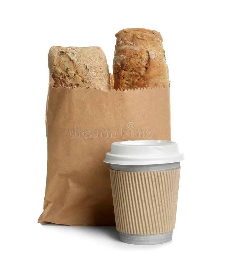 Paper bag with bread and cup of coffee on white background. royalty free stock images