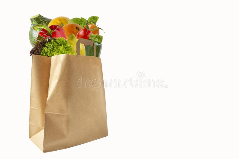 A paper bag filled with vegetables and fruits. Purchase of products.Isolated objects on white background royalty free stock images