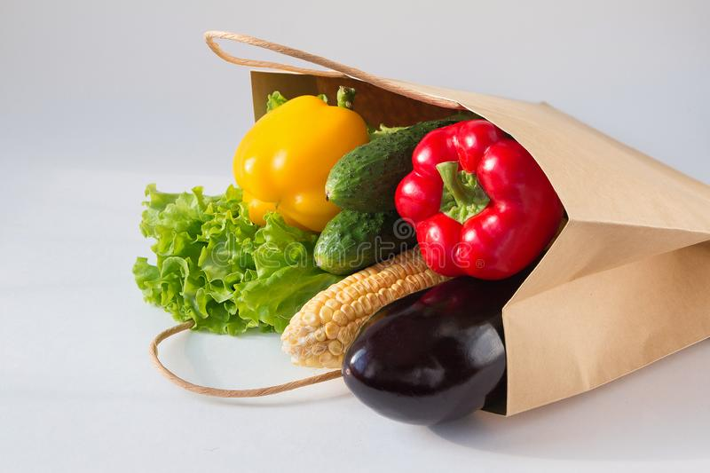 Paper bag full of fresh vegetables on light background. Sweet pepper, cucumbers, corn, salad, eggplant. Side view. stock photos