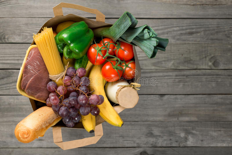 Paper bag of groceries on wooden table with copy space royalty free stock photography