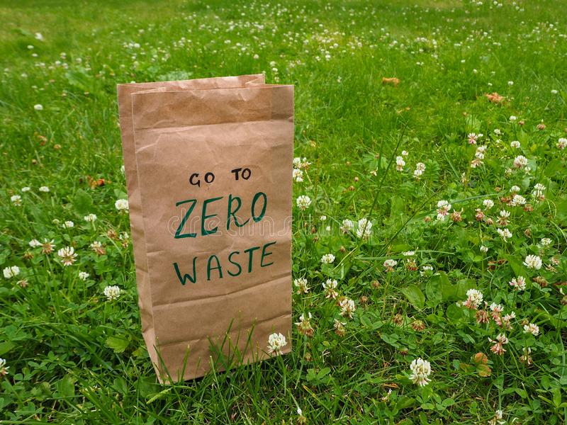 A paper bag with handwritten words `Go to zero waste` on it among clover and green grass with copy space. stock image
