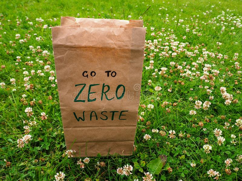 A paper bag with handwritten words `Go to zero waste` on it stands among clover and green grass. stock images