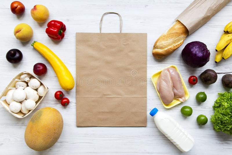 Paper bag of healthy organic food on white wooden background. Cooking food background. Flat-lay of fresh fruits, veggies, greens,. Meat, milk, view from above royalty free stock photo