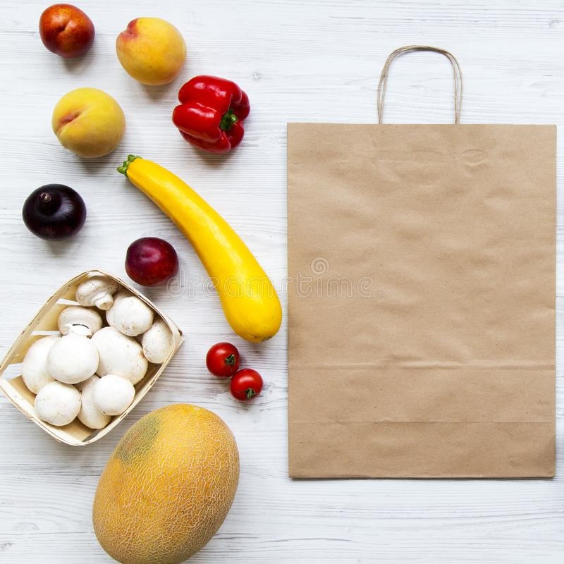 Paper bag of healthy organic food on white wooden surface. Cooking food background. Flat-lay of fresh fruits, vegetables, top view stock photos