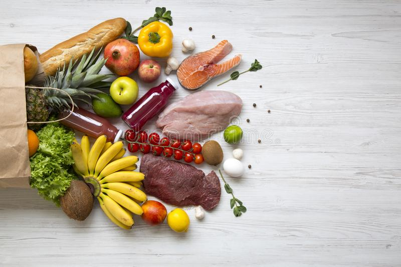 Paper bag of healthy raw food on white wooden table. Cooking food background. Flat-lay of fresh fruits, veggies, greens, different. Meat, top view, copy space royalty free stock photo