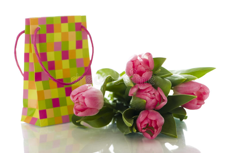 Paper bag present with tulips. Isolated on white background royalty free stock photography