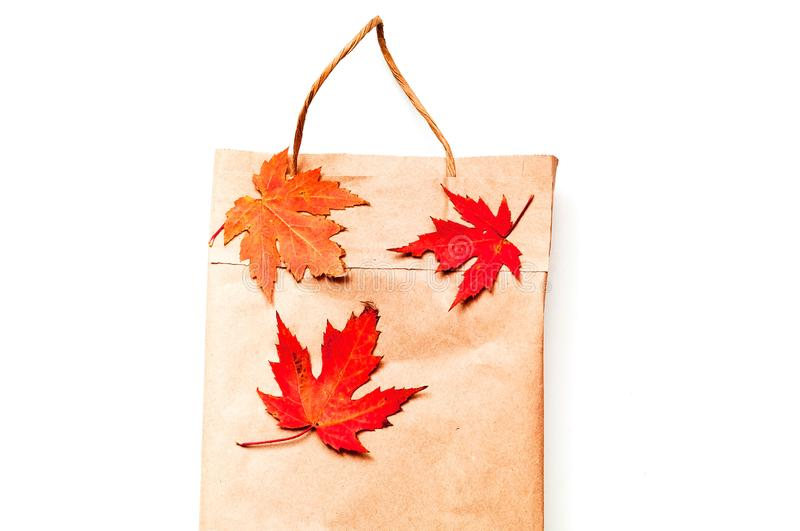 Paper bag for products with autumn leaves. Eco packaging concept. Close-up, copy space stock photo