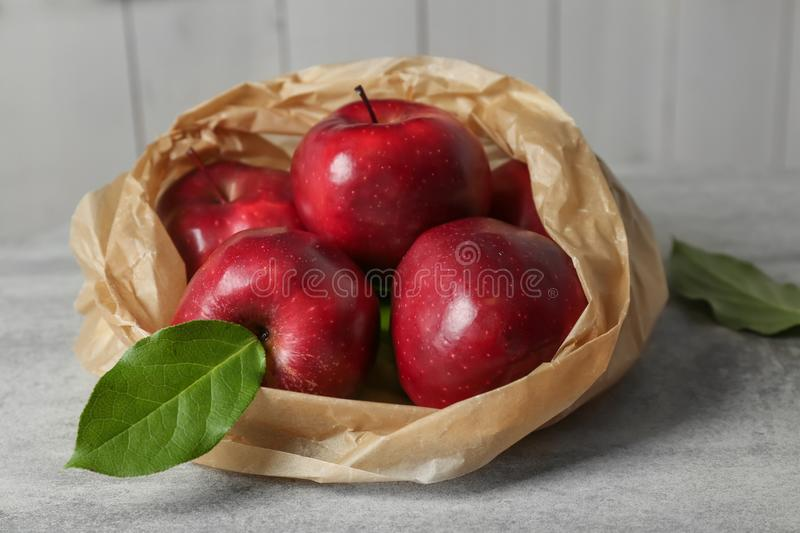 Paper bag with ripe red apples stock photography