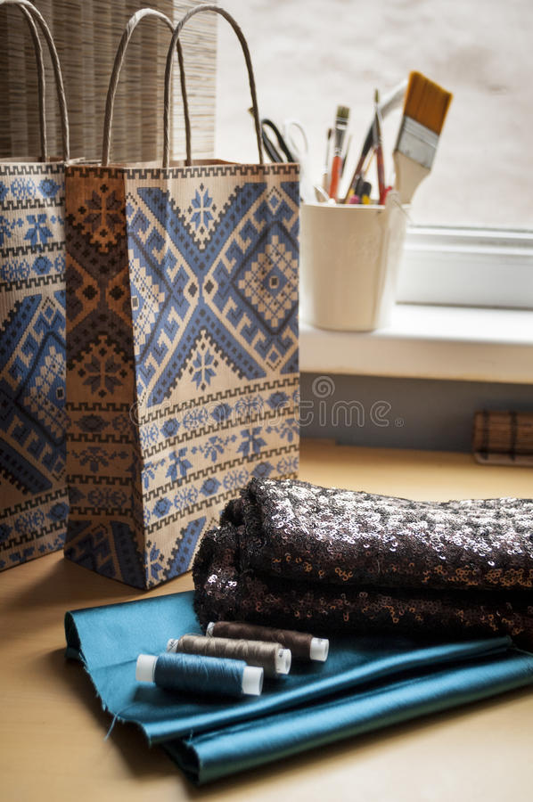 Paper bag and textile whits threads, gift. Bag on table royalty free stock image