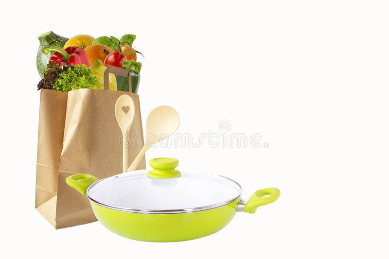 Paper bag with vegetables and fruits,green frying pan and wooden spoons. Purchase of products.Isolated objects on white background. Paper bag with vegetables and stock photography