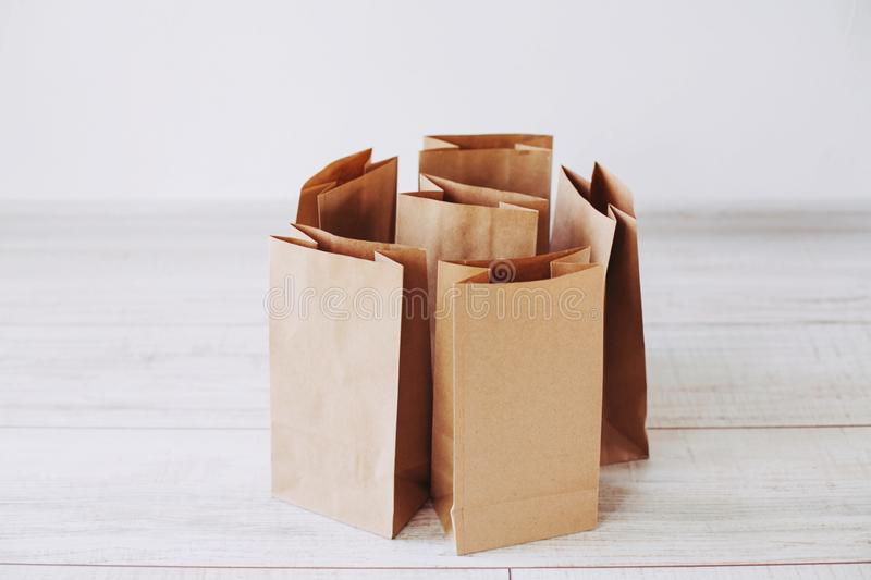 Ecologic craft package. Paper bags on light wooden floor. Simple brown paper bags for lunch or meal. The layout for the design. Environmental ship packages royalty free stock photos